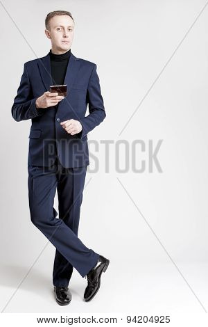 Full Length Portrait Of Caucasian Businessman In Stylish Blue Suite Posing With Cell Phone