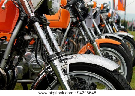 Row of motorbikes in a field