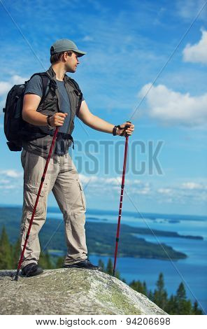 Young man tourist with backpack and sticks standing on mountain top and looking aside.