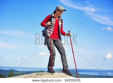 Young woman tourist walking on mountain with sticks. On blue sky background.