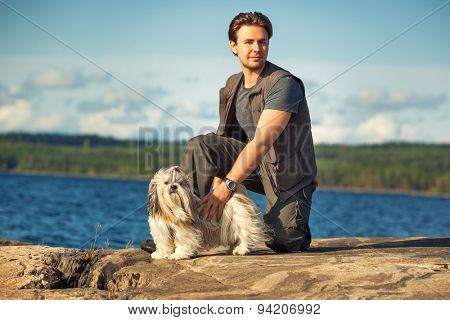 Young man tourist with shih-tzu dog on lake shore.