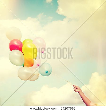 Girl hand holding multicolored balloons vintage color tone
