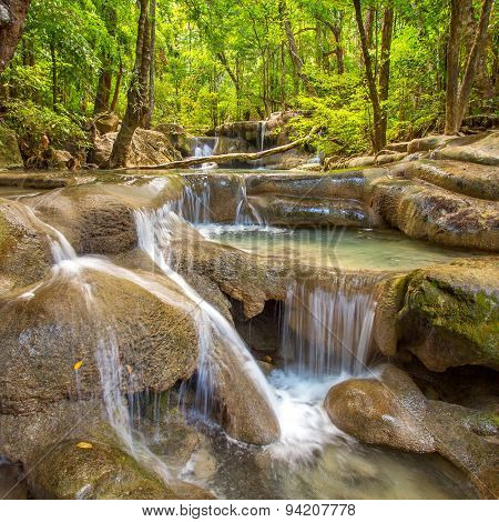The long exposure image of a beautiful cascade river in the forest. Erawan National Park, Kanchanaburi, Thailand