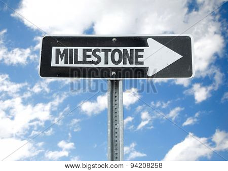 Milestone direction sign with sky background