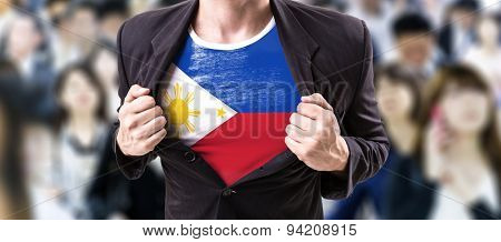 Businessman stretching suit with Philippines Flag with a crowd people on background