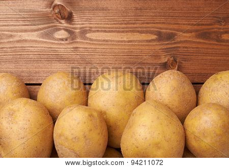 Pile of potatoes over the wooden surface