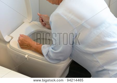 Woman Getting Sick Over A Toilet Bowl