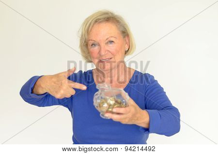Smiling Senior Woman Holding A Glass Piggy Bank