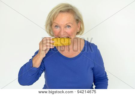 Elderly Lady Enjoying Fresh Corn On The Cob