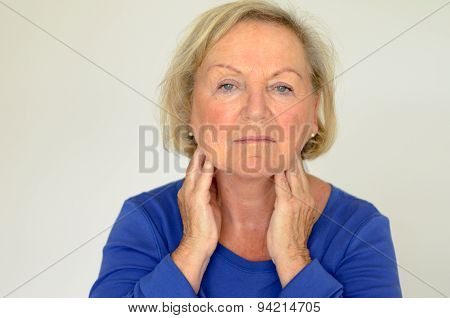 Thoughtful Elderly Woman With Her Hands To Her Neck