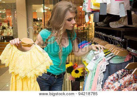 elegant woman choosing dress in retail store