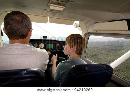 Joung Boy Is Flying Aircraft Assisted By A Trainer