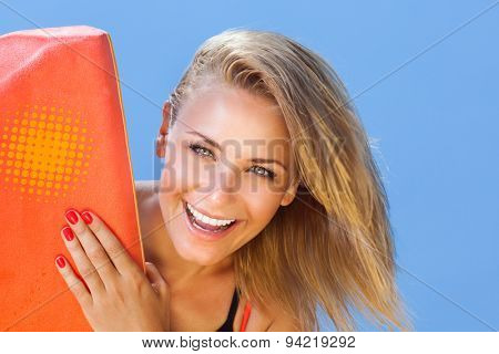 Closeup portrait beautiful cheerful woman peeping from behind surfboard, sportive lifestyle, enjoying active summer vacation on the beach