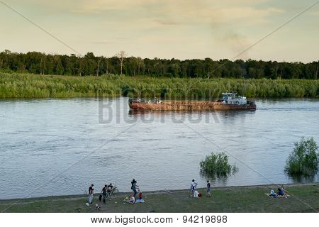 People Relaxing On River Bank And Boat