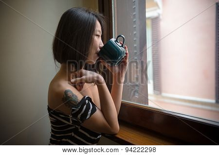Beautiful Asian Woman Drinking With Blue Cup Looking At Window