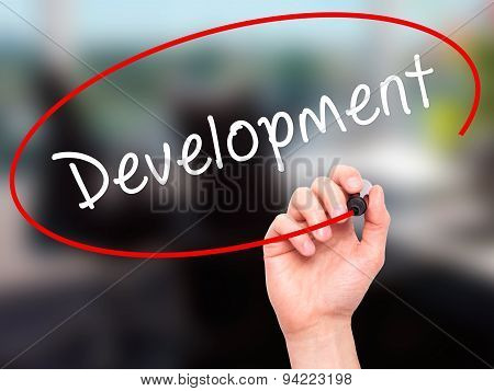Man Hand writing Development with black marker on visual screen.