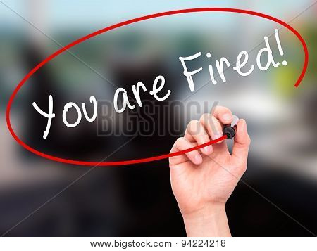 Man Hand writing You are Fired! with black marker on visual screen.