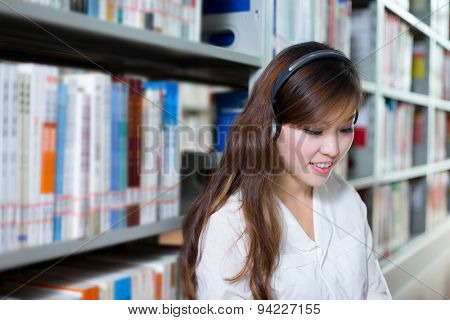 Asian beautiful female student listen to music in library
