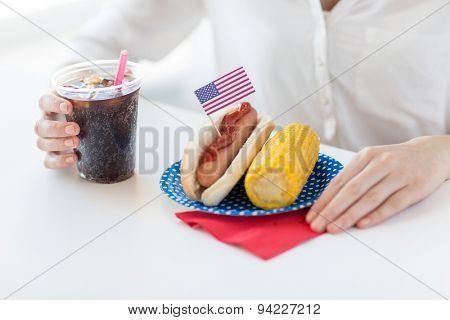 american independence day, celebration, patriotism and holidays concept - close up of woman hands with hot dog and corn holding coca cola drink in plastic cup on 4th july party