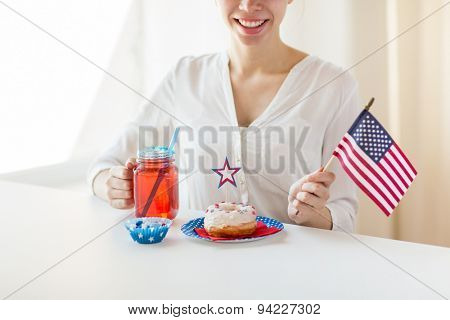 independence day, celebration, patriotism and holidays concept - close up of happy woman with donut celebrating 4th july, holding american flag and drinking juice from glass mason jar or mug at home