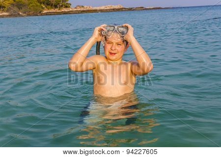 Young Boy In The Beautiful Clear Sea Starts Snorkeling