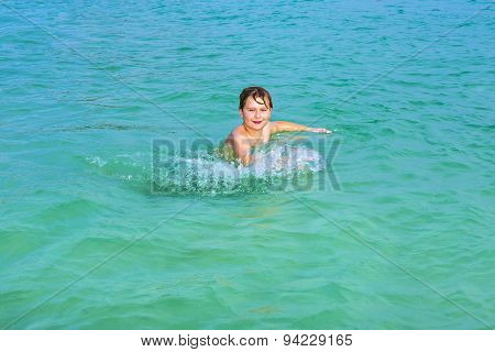 Handsome Boy Enjoys Sputtering With His Hand In The Tropical Ocean