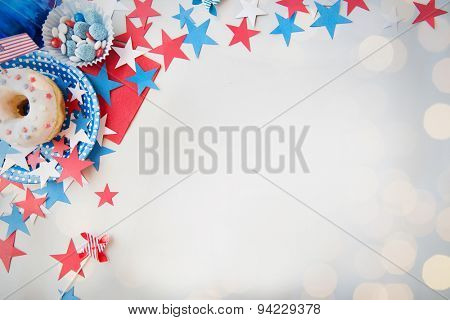 american independence day celebration, patriotism and holidays concept - close up of glazed sweet donut with candies in disposable tableware and stars at 4th july party from top over lights background