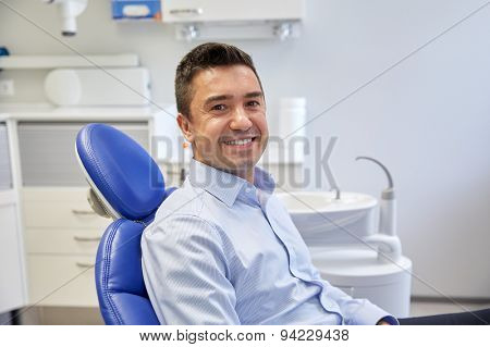 people, medicine, stomatology and health care concept - happy male patient sitting on dental chair at clinic office
