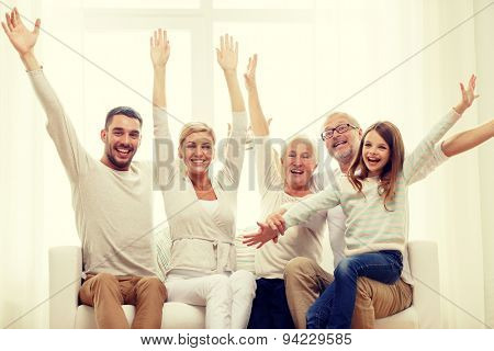 family, happiness, generation and people concept - happy family sitting on sofa and rising hands at home