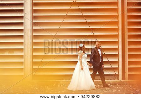 Bride And Groom Against A Striped Wall