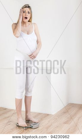 pregnant woman standing on a weight scale with a tape measure