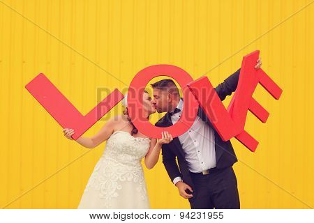 Bride And Groom Holding Big Love Letters
