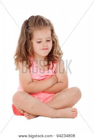 Angry little girl with three year old sitting on the floor isolated on a white background