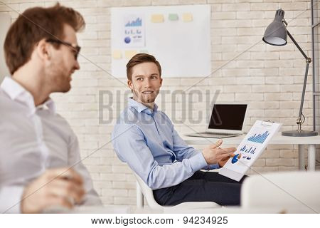 Successful businessman explaining charts to colleague in office