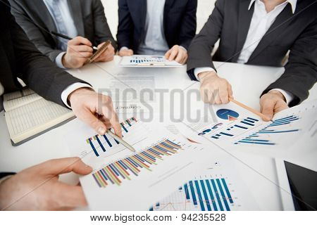 Two co-workers pointing at financial documents with data at meeting