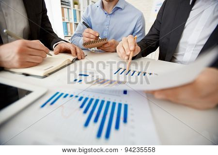 Businessman pointing at paper with chart while explaining it to colleagues at workplace