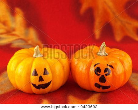 Mini Pumpkins With Funny Faces On A Red Autumn Cloth Background