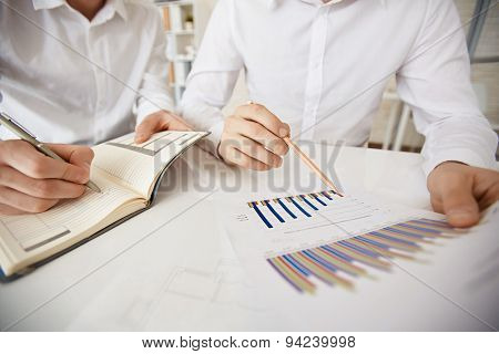 Hand of businessman with pencil pointing at data in document while his colleague making notes