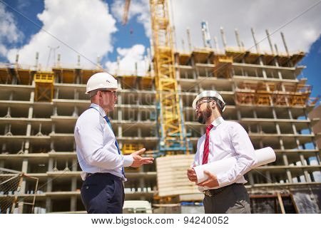 Two businessmen in helmets talking on background of building structure