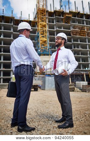 Successful young architects handshaking near building structure