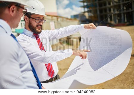 Male architects in helmets discussing blueprint outside
