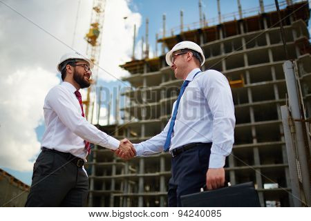 Two architects handshaking on background of new construction