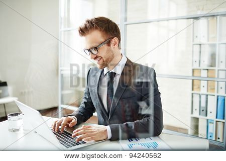 Successful young businessman networking in office