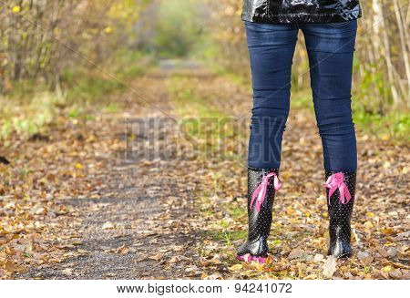 detail of standing woman wearing black rubber boots