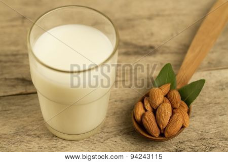 Peeled Almonds In A Spoon C Leaves And A Glass Of Milk On Wooden Table