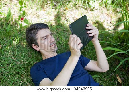 casual man working with a tablet pc, outdoor