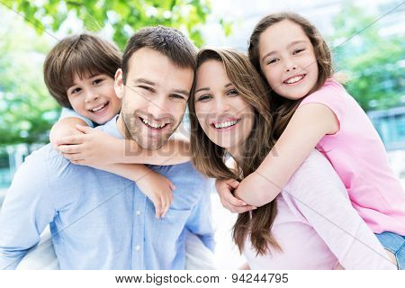 Parents giving kids piggyback ride