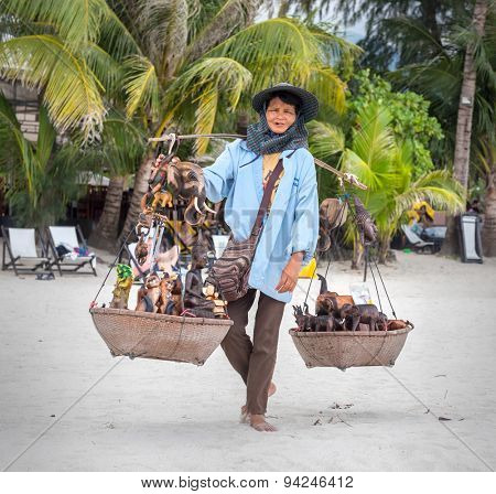 Koh Chang, THAILAND - MARCH 12: An elderly woman sells to tourists souvenirs on the beach, Thailand, on March 12, 2015.