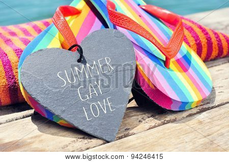 the sentence summer gay love written in a heart-shaped slate stone and a pair of rainbow flip-flops and a beach towel on a boardwalk above the ocean