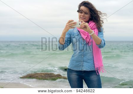 Young Smiling Woman With Curly Hair In A Denim Shirt Makes The Photo Self